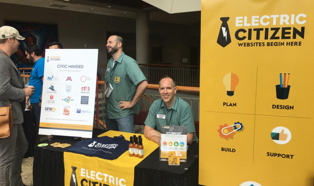Dan and Adam talking to visitors at the Electric Citizen sponsor table, with large gold banners and signage promoting the company