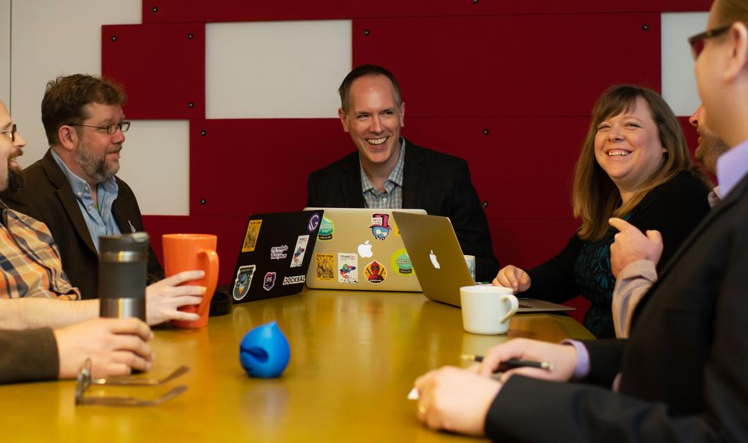 staff talking and laughing around conference table