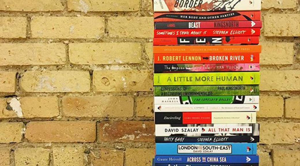 stack of published paperback books beside a brick wall