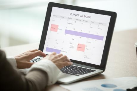 Businesswoman planning day using digital calendar on laptop