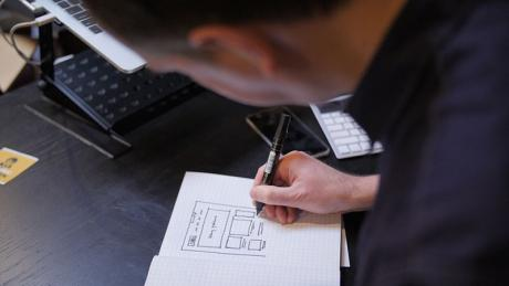 Dan sketching a webpage layout on paper