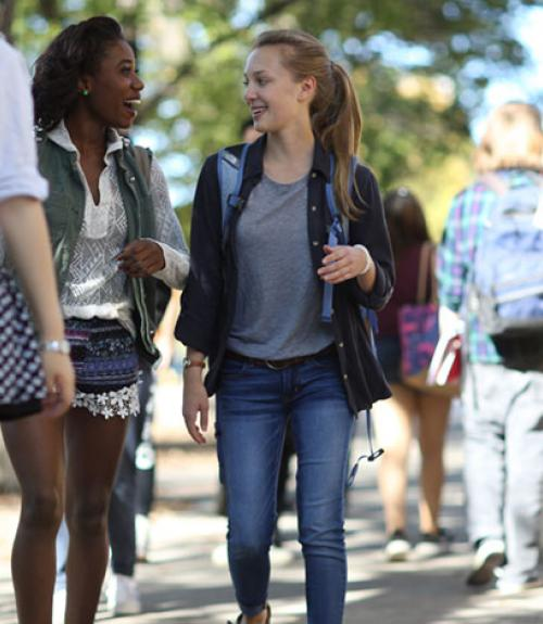 Two young women talking and walking on Morris campus