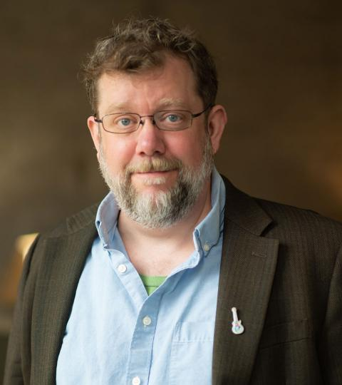 photo of tim broeker wearing a blue dress shirt and dark green jacket
